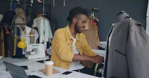 Δημιουργικός σχεδιαστής που μετρά τα χειροποίητα ενδύματα στο ομοίωμα που απολαμβάνει το χαμόγελο εργασίας απόθεμα βίντεο