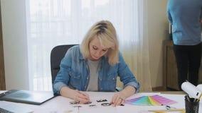Δημιουργικός σχεδιαστής που σκιαγραφεί τα σχέδια λογότυπων φιλμ μικρού μήκους