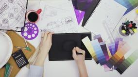 Δημιουργικός σχεδιαστής που χρησιμοποιεί την ταμπλέτα γραφικής παράστασης εργαζόμενος στον πίνακά της απόθεμα βίντεο