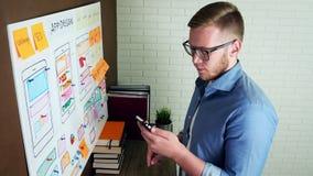 Δημιουργικός σχεδιαστής UX που κάνει την έρευνα δυνατότητας χρησιμοποίησης για την κινητή εφαρμογή απόθεμα βίντεο