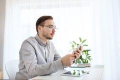 Δημιουργικό αρσενικό εργαζομένων γραφείων στο smarphone Στοκ Φωτογραφίες