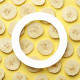 Δημιουργικό θερινό σχέδιο φιαγμένο από φέτα μπανανών στο κίτρινο υπόβαθρο κρητιδογραφιών στοκ φωτογραφία