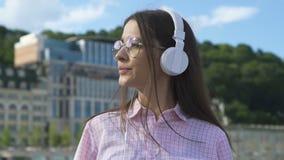 Δημιουργικό θηλυκό στα ακουστικά που απολαμβάνει την εξόρμηση πόλεων, έμπνευση μουσικής, ελευθερία απόθεμα βίντεο