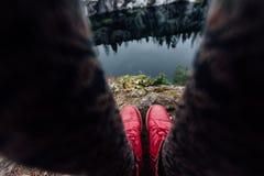 Δημιουργικό κορίτσι που στέκεται στην άκρη ενός γραφικού απότομου βράχου Τουρίστας στα τζιν και τα κόκκινα πάνινα παπούτσια μποτώ Στοκ φωτογραφία με δικαίωμα ελεύθερης χρήσης