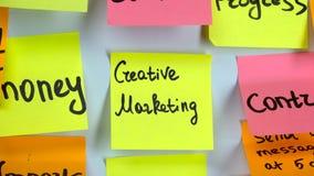 Δημιουργικό μάρκετινγκ επιγραφής σε μια κίτρινη αυτοκόλλητη ετικέττα στον πίνακα απόθεμα βίντεο