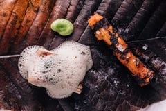 Δημιουργικό πρόστιμο που δειπνεί: Το κάλυμμα ψαριών με το μαγειρικό αφρό εξυπηρετεί με το μπιζέλι και η ψημένη στη σχάρα ρίζα με  Στοκ Εικόνες