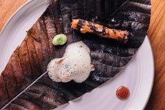 Δημιουργικό πρόστιμο που δειπνεί: Το κάλυμμα ψαριών με το μαγειρικό αφρό εξυπηρετεί με το μπιζέλι και η ψημένη στη σχάρα ρίζα με  Στοκ Εικόνα