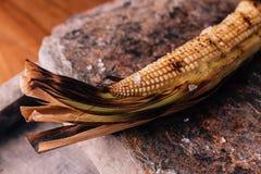 Δημιουργικό πρόστιμο που δειπνεί: Ψημένος στη σχάρα αστακός και ψημένο καλαμπόκι που εξυπηρετούνται στο φυσικό πιάτο μορφής πετρώ Στοκ Εικόνα