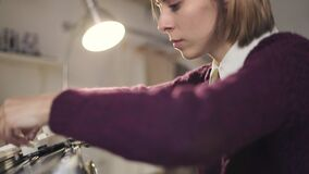 Δημιουργικό ρυθμίζοντας νήμα γυναικών στη μηχανή αργαλειών για το ύφασμα στο εργαστήριο φιλμ μικρού μήκους
