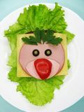 Δημιουργικό σάντουιτς τροφίμων με το λουκάνικο και τυρί που εξυπηρετείται στο μαρούλι Στοκ Εικόνες