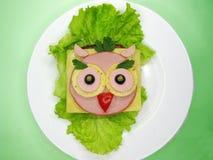 Δημιουργικό σάντουιτς τροφίμων με το λουκάνικο και τυρί που εξυπηρετείται στο μαρούλι Στοκ Εικόνα
