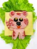 Δημιουργικό σάντουιτς τροφίμων με το λουκάνικο και τυρί που εξυπηρετείται στο μαρούλι Στοκ εικόνες με δικαίωμα ελεύθερης χρήσης