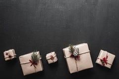 Δημιουργικό χόμπι Συσκευασία των σύγχρονων κιβωτίων χριστουγεννιάτικου δώρου στο μοντέρνο καφετί έγγραφο με την κορδέλλα Στοκ Φωτογραφία