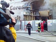 Δημοσιογράφος ειδήσεων και να στηριχτεί στην πυρκαγιά στοκ φωτογραφίες