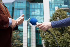 Δημοσιογράφος που παίρνει συνέντευξη από τον επιχειρηματία, εταιρικό κτήριο στο υπόβαθρο Στοκ Εικόνες