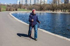 Δημοφιλής αθλητισμός γύρω από το κόσμος-σκανδιναβικό περπάτημα μια ηλικιωμένη γυναίκα πηγαίνει στο πάρκο άνοιξη Ενεργοί άνθρωποι  στοκ εικόνες με δικαίωμα ελεύθερης χρήσης