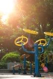 Δημόσια παιδική χαρά με τις εγκαταστάσεις άσκησης ενάντια στην υγιή έννοια τρόπου ζωής & άσκησης ήλιων Στοκ Φωτογραφία