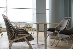 Δημόσιοι καρέκλες δωματίων και πίνακες, σαλόνι στον αερολιμένα, θερινό πεζούλι Στοκ Εικόνες