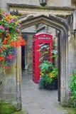 Διάβαση πεζών μέσω της σχηματισμένης αψίδα πόρτας, λουλούδια, τηλεφωνικός θάλαμος, εσωτερικό κολλέγιο Magdalen, Οξφόρδη στοκ εικόνες