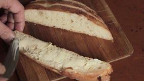 Διάδοση του βουτύρου σε ένα κομμάτι του αγροτικού ψωμιού σίτου σε έναν ξύλινο πίνακα φιλμ μικρού μήκους