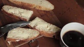 Διάδοση του βουτύρου σε ένα κομμάτι του αγροτικού ψωμιού σίτου σε έναν ξύλινο πίνακα απόθεμα βίντεο