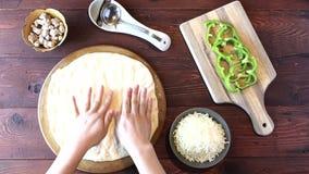 Διάδοση του τυριού μοτσαρελών σε μια πίτσα απόθεμα βίντεο