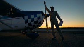 Διάδρομος απογείωσης ηλιοβασιλέματος με έναν αρσενικό μηχανικό υπηρεσίας που καθαρίζει το αεροπλάνο απόθεμα βίντεο