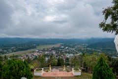Διάδρομος του αερολιμένα στην επαρχία με το χωριό και της λίμνης στο λόφο στη νεφελώδη ημέρα με το μαλακό φως του ήλιου στοκ φωτογραφία με δικαίωμα ελεύθερης χρήσης