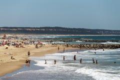 Διάσημη παραλία στον ωκεανό όπου κάνοντας ηλιοθεραπεία και στηργμένος πολλούς ανθρώπους, Λισσαβώνα, Πορτογαλία Στοκ Φωτογραφίες