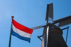Διάσημοι παλαιοί ολλανδικοί ανεμόμυλος και σημαία των Κάτω Χωρών Στοκ Φωτογραφία