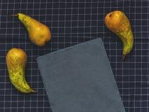 Διάσκεψη τριών πράσινη αχλαδιών, μια τέμνουσα πλάκα πινάκων σχετικά με μαύρο clo Στοκ εικόνες με δικαίωμα ελεύθερης χρήσης