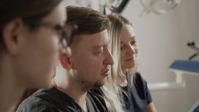 Διάσκεψη των γιατρών της οδοντιατρικής Ο οδοντίατρος συζητά τις ακτίνες X του ασθενή τους σε μια συνεδρίαση απόθεμα βίντεο