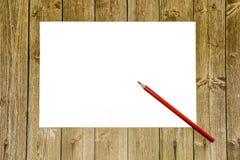 Διάστημα αντιγράφων σε ένα ξύλινο υπόβαθρο, ένα άσπρο φύλλο του εγγράφου με ένα κόκκινο μολύβι θέση για τη διαφήμιση και τα αρχεί στοκ εικόνα