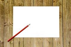 Διάστημα αντιγράφων σε ένα ξύλινο υπόβαθρο, ένα άσπρο φύλλο του εγγράφου με ένα κόκκινο μολύβι θέση για τη διαφήμιση και τα αρχεί στοκ εικόνες