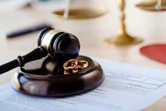 Διάταγμα διαζυγίου μέσα και δύο σπασμένα γαμήλια δαχτυλίδια gavel δικαστών στοκ εικόνα