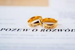 Διάταγμα διαζυγίου σε πολωνική γλώσσα και δύο σπασμένα γαμήλια δαχτυλίδια στοκ εικόνα