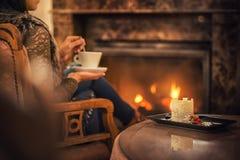 Διάταξη θέσεων γυναικών κοντά στην εστία και το φλιτζάνι του καφέ κατανάλωσης και κατανάλωση του όμορφου χειμερινού επιδορπίου με στοκ φωτογραφία με δικαίωμα ελεύθερης χρήσης