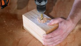 Διάτρυση μιας τρύπας σε έναν τετραγωνικό ξύλινο φραγμό απόθεμα βίντεο