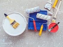 Διάφορα αντικείμενα για τη ζωγραφική των εργασιών - το α μπορεί του χρώματος, οι βούρτσες, κύλινδροι, spatula βρίσκονται στο τσιμ Στοκ εικόνα με δικαίωμα ελεύθερης χρήσης