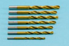 Διάφορα δυαδικά ψηφία τρυπανιών μεγέθους χρυσά στο μπλε Στοκ Εικόνες