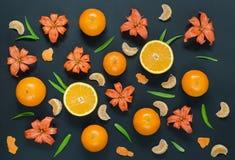 Διάφορα εσπεριδοειδή και πορτοκαλιοί κρίνοι σε ένα μαύρο υπόβαθρο Στοκ φωτογραφία με δικαίωμα ελεύθερης χρήσης