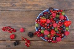 Διάφορα θερινά φρέσκα μούρα σε ένα κύπελλο στον αγροτικό ξύλινο πίνακα Αντιοξειδωτικοοι, detox διατροφή, οργανικά φρούτα Τοπ όψη Στοκ Φωτογραφίες