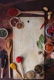 Διάφορα ινδικά καρυκεύματα στα ξύλινα κουτάλια, τους σπόρους, τα χορτάρια και τα καρύδια και τον κενό ξύλινο πίνακα Στοκ Φωτογραφία
