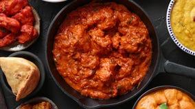 Διάφορα ινδικά πιάτα σε έναν πίνακα Πικάντικο κοτόπουλο Tikka Masala στο τηγάνι σιδήρου απόθεμα βίντεο