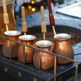 Διάφορα καπνισμένα δοχεία για την κατασκευή του τουρκικού καφέ είναι στάση σε έναν πίνακα μετάλλων Στοκ Εικόνα