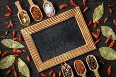 Διάφορα καρυκεύματα στα ξύλινα κουτάλια στο σκοτεινό πίνακα πετρών στοκ φωτογραφία με δικαίωμα ελεύθερης χρήσης