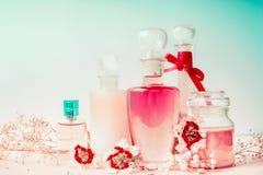 Διάφορα καλλυντικά δέρμα, τρίχες και προϊόντα προσοχής σωμάτων στα μπουκάλια στο ρόδινο τυρκουάζ μπλε υπόβαθρο, μπροστινή άποψη Κ Στοκ Εικόνες