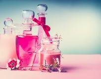 Διάφορα καλλυντικά δέρμα, τρίχες και προϊόντα προσοχής σωμάτων στα μπουκάλια στο ρόδινο τυρκουάζ μπλε υπόβαθρο, μπροστινή άποψη,  Στοκ Φωτογραφίες