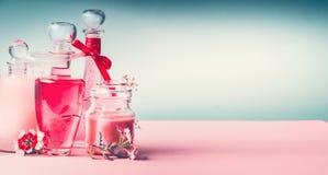 Διάφορα καλλυντικά δέρμα, τρίχες και προϊόντα προσοχής σωμάτων στα μπουκάλια στο ρόδινο τυρκουάζ μπλε υπόβαθρο, μπροστινή άποψη,  Στοκ φωτογραφία με δικαίωμα ελεύθερης χρήσης