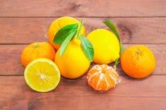 Διάφορα μανταρίνια, λεμόνια και πορτοκάλια σε ένα ξύλινο surfac Στοκ Φωτογραφίες